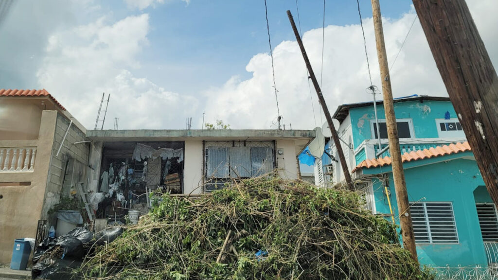 Agentes de la Policía colaboran con la limpieza de una residencia en Coamo.