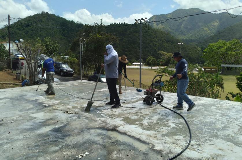 Agentes de la Policía realizan trabajos de limpieza en una residencia de Guayama. (Suministrada)